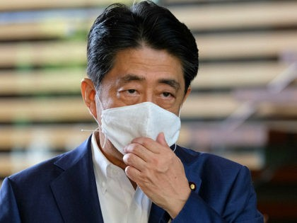 TOPSHOT - Japan's Prime Minister Shinzo Abe wearing a face mask arrives at the Prime Minister's office in Tokyo on August 24, 2020. - Abe earlier in the day returned to hospital on August 24 for more medical checks, a government spokesman said, a week after a first visit that …