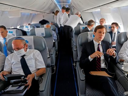 TOPSHOT - US Presidential Adviser Jared Kushner (C) and US National Security Adviser Robert OBrien (R) and Head of Israel's National Security Council Meir Ben-Shabbat (L) sit in their seat in the El Al's airliner, which is carrying a US-Israeli delegation to the UAE following a normalisation accord, upon landing …