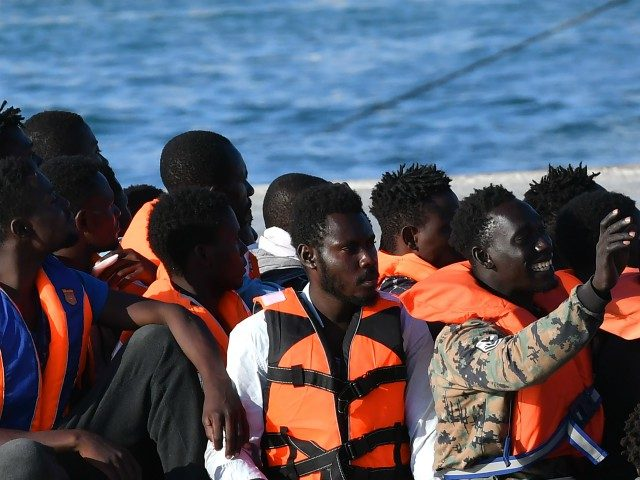 Migrants from Lybia wait to disembark from Italy's Guardia Costiera (Coast Guard) boat in the Italian Pelagie Island of Lampedusa on July 31, 2020. - The reception centre on the island is already overcrowded with migrants who have been arriving daily by the hundreds in recent weeks. (Photo by Alberto …