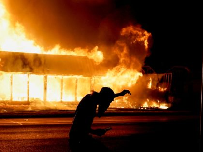 A protester walks past a building ablaze during protests Monday, Aug. 24, 2020, in Kenosha, Wis., sparked by the shooting of Jacob Blake by a Kenosha Police officer on Sunday. (AP Photo/Morry Gash)