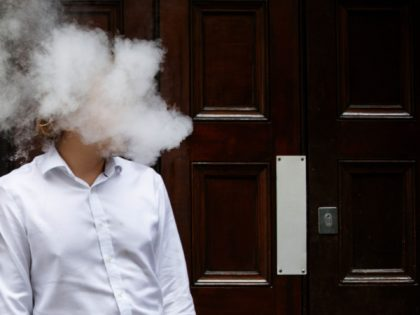 "A smoker is engulfed by vapours as he smokes an electronic vaping machine during lunch time in central London on August 9, 2017. - World stock markets and the dollar slid Wednesday after US President Donald Trump warned of ""fire and fury"" in retaliation to North Korea's nuclear ambitions, sending …"