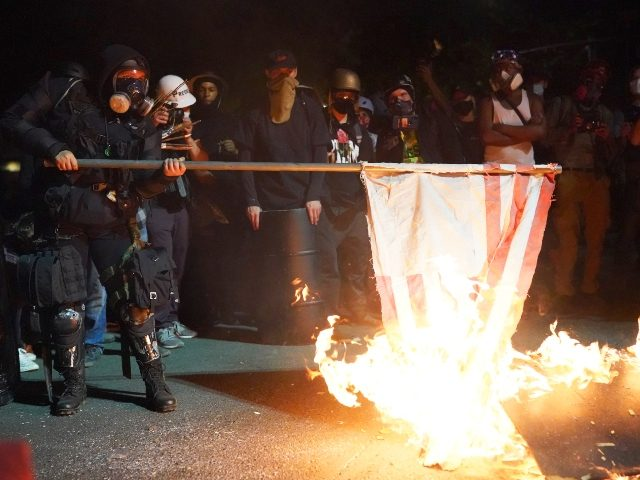 PORTLAND, OR - AUGUST 1: A protester burns an American flag in front of the Mark O. Hatfield U.S. Courthouse in the early morning on August 1, 2020 in Portland, Oregon. Friday was the second night in a row without police intervention, following weeks of clashes between federal officers and …