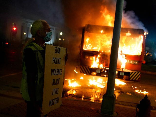 A protester stands near a burning garbage truck outside the Kenosha County Courthouse, late Monday, Aug. 24, 2020, in Kenosha, Wis. Protesters converged on the county courthouse during a second night of clashes after the police shooting of Jacob Blake a day earlier turned Kenosha into the nation's latest flashpoint …