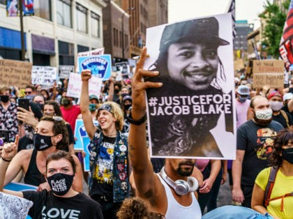 Protesters march near the Minneapolis 1st Police precinct during a demonstration against police brutality and racism on August 24, 2020 in Minneapolis, Minnesota. - It was the second day of demonstrations in Kenosha after video circulated Sunday showing the shooting of Jacob Blake -- multiple times, in the back, as he …