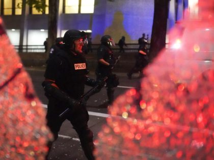 PORTLAND, OR - AUGUST 25: Portland police walk past the shattered glass of a bus stop while dispersing a crowd of about 150 people from Portland City Hall on August 25, 2020 in Portland, Oregon. Crowds chanted in support of Kenosha Wisconsin on the 90th night of protests Tuesday, where …