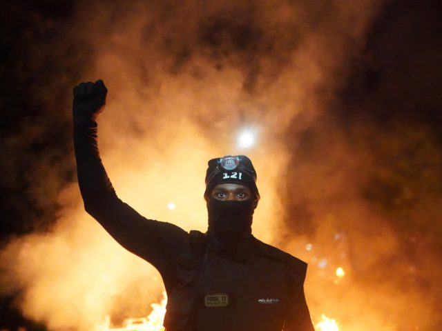PORTLAND, OR - AUGUST 23: A protester holds his fist in the air during a protest against racial injustice and police brutality early in the morning on August 23, 2020 in Portland, Oregon. Hundreds of protesters clashed with police Saturday night following a rally in east Portland. (Photo by Nathan …
