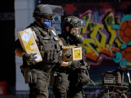 "Seattle police officers carry boxes with warning stickers and a slip of paper that reads ""blast balls"" as police clash with protesters following a ""Youth Day of Action and Solidarity with Portland"" demonstration in Seattle, Washington on July 25, 2020. - Police in Seattle used flashbang grenades and pepper spray …"