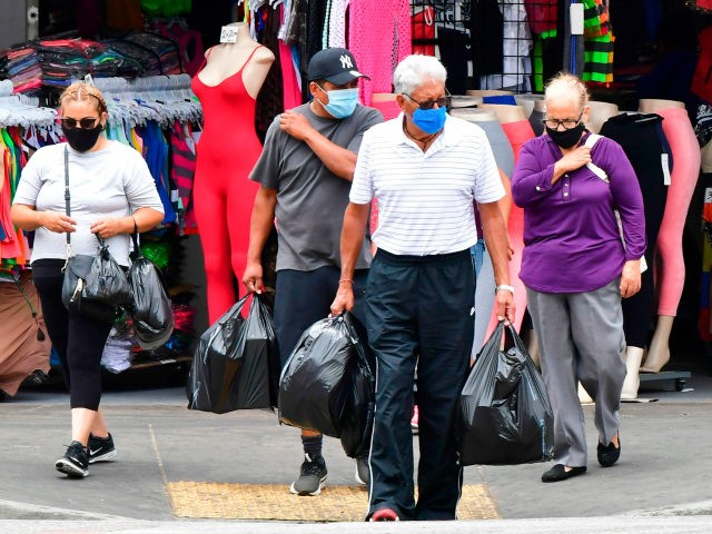 People wear facemasks while shopping in Los Angeles, California on July 1, 2020, after indoor restaurants, bars and movie theaters across much of California were ordered to close for at least three weeks. - Some Californian restaurants shut their doors Wednesday as new measures to tackle the coronavirus pandemic threaten …