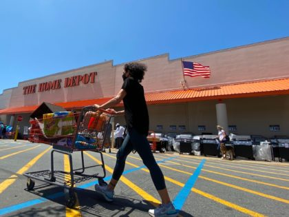A shopper wearing a facemask pushes her cart while people wait in line to enter The Home Depot in Marina Del Rey, California on May 22, 2020, amid the novel coronavirus pandemic. (Photo by Chris DELMAS / AFP) (Photo by CHRIS DELMAS/AFP via Getty Images)