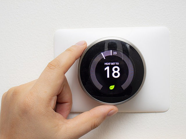 Smart Thermostat with a person saving energy with a soft shadow