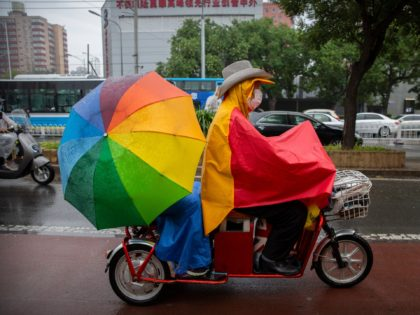 A man wearing a face mask to protect against the spread of the new coronavirus rides a scooter in the rain in Beijing, Thursday, July 9, 2020. (AP Photo/Mark Schiefelbein)
