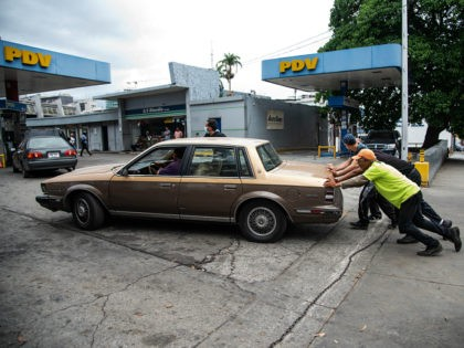 CARACAS, VENEZUELA - JUNE 01: Four men push a car that ran out of gas into a gas station on June 1, 2020 in Caracas, Venezuela. After 77 days, Maduro Administration eases the restrictions against COVID-19, allowing certain activities to reopen. From today, an official limit has been set for …