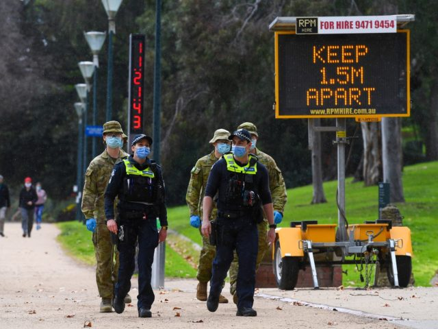 Police officers and soldiers patrol a popular running track in Melbourne on August 4, 2020 after the state announced new restrictions as the city battles fresh outbreaks of the COVID-19 coronavirus. - Australia's Victoria state imposed fresh, sweeping restrictions on August 2, 2020, including a curfew in Melbourne for the …