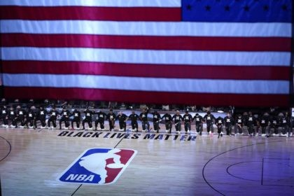 Members of the Orlando Magic and Brooklyn Nets kneel around a Black Lives Matter logo during the national anthem before the start of an NBA basketball game Friday, July 31, 2020, in Lake Buena Vista, Fla. (AP Photo/Ashley Landis, Pool)