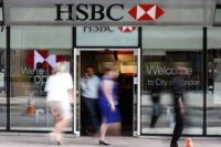 In this Aug. 28, 2015, file photo, people walk past a branch of HSBC bank in London. Europe's biggest bank, HSBC, has reported Monday, Aug. 3, 2020, its net profit plummeted 96% in the second quarter of this year as lower interest rates combined with the downturn due to the …