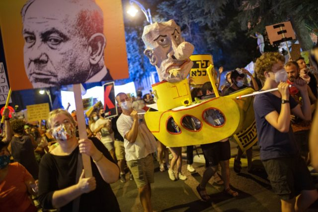 Demonstrators chant slogans and hold signs during a rally against Israel's Prime Minister Benjamin Netanyahu outside his residence in Jerusalem, Saturday, Aug 1, 2020. Protesters demanded that the embattled Israeli leader to resign as he faces a trial on corruption charges and grapples with a deepening coronavirus crisis. (AP Photo/Oded …
