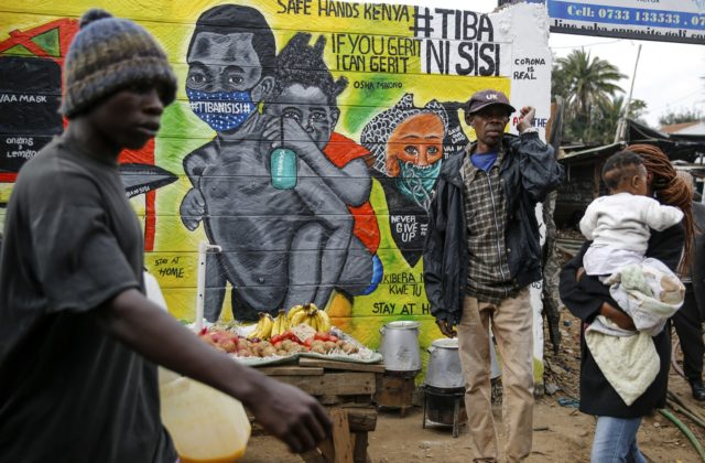 """In this July 8, 2020, file photo, people walk past an informational mural warning people about the dangers of the new coronavirus and how to prevent transmission, with words in Swahili reading """"We are the Cure"""", painted by youth artists from the Uweza Foundation, in the Kibera slum, or informal …"""