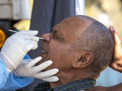 A man reacts as a health worker collects a sample for coronavirus testing during the screening and testing campaign aimed to combat the spread of COVID-19, in Eldorado Park outside of Johannesburg, South Africa, Monday, Aug. 3, 2020. (AP Photo/Themba Hadebe)