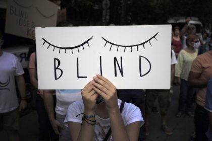 """A protester holds a poster in front of the German Embassy in Sofia, Bulgaria, Wednesday, Aug. 12, 2020. Several hundred anti-government protesters gathered in front of Germany's embassy in Sofia, calling on Berlin and Brussels to """"open their eyes"""" to widespread corruption in Bulgaria. During the peaceful protest, dubbed """"Eyes …"""