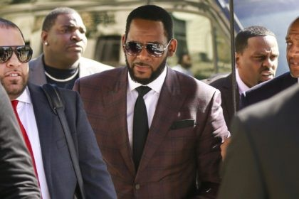 In this June 26, 2019 file photo, R&B singer R. Kelly, center, arrives at the Leighton Criminal Court building for an arraignment on sex-related felonies in Chicago. Federal prosecutors announced charges Wednesday, Aug. 12, 2020, against three men accused of threatening and intimidating women who have accused Kelly of abuse, …
