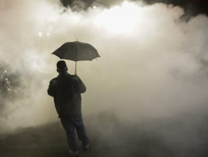 In this July 25, 2020, file photo, a protester carries an umbrella as federal police officers deploy tear gas during a protest at the Mark O. Hatfield U.S. Courthouse in Portland, Ore. Federal agents have left Portland, but city officials are still learning about and cleaning tear gas residue that …