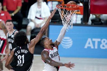 Portland Trail Blazers' Damian Lillard, right, goes up for a shot against Brooklyn Nets' Jarrett Allen (31) during the first half of an NBA basketball game Thursday, Aug. 13, 2020 in Lake Buena Vista, Fla. (AP Photo/Ashley Landis, Pool)