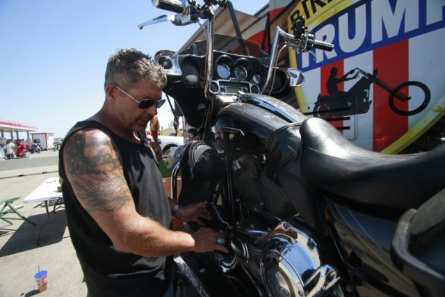 Chris Cox, the founder of Bikers for Trump, examines his motorcycle on Saturday, Aug. 8, 2020, outside the Bikers for Trump trailer he brought to the Sturgis Motorcycle Rally, in Sturgis, S.D. The group has taken advantage of recent motorcycle rallies, which have been some of the largest mass gatherings …