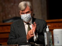 Sen. Sheldon Whitehouse, D-RI, wears a facemask and cleans his hands with a disinfecting wipe as he arrives during the start of a Senate Judiciary Committee oversight hearing on Capitol Hill in Washington,DC on August 5, 2020, to examine the Crossfire Hurricane investigation. (Photo by Carolyn Kaster / POOL / …