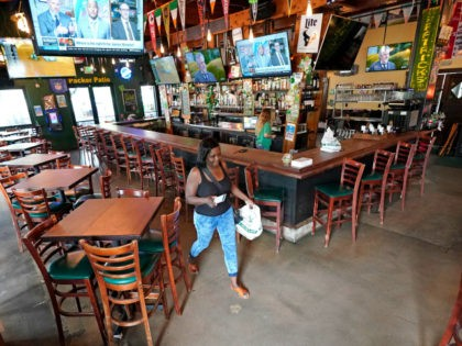 Pam Jones picks up her takeaway food order at Mo's Irish Pub on St. Patrick's Day, Tuesday, March 17, 2020, in Houston. Houston area bars and restaurants have been ordered to follow new restrictions for the next 15 days in an effort to curb coronavirus exposure. Bars and nightclubs must …