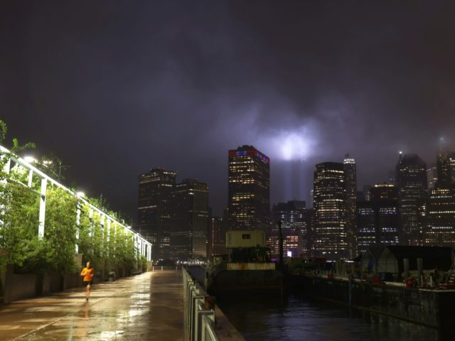 NEW YORK, NEW YORK - SEPTEMBER 10: A man jogs in Brooklyn Bridge Park as the 9/11 Tribute in Light shines above the lower Manhattan skyline on September 10, 2020 in New York City. The National September 11 Memorial & Museum's annual Tribute in Light was initially cancelled this year …