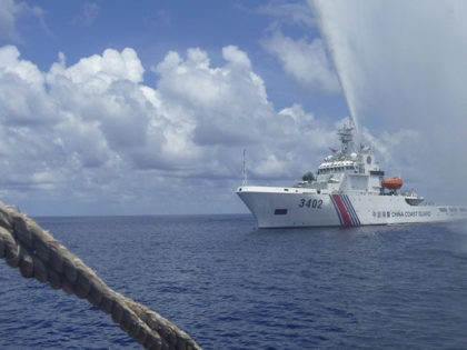 FILE - In this Sept. 23, 2015, file photo, Chinese Coast Guard members approach Filipino fishermen as they confront each other off Scarborough Shoal in the South China Sea, also called the West Philippine Sea. The Philippine defense chief says aerial surveillance shows Chinese coast guard ships are still guarding …