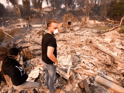 Alexander Tobolsky, right, and his girl friend Dina Arias, return to his home where burned out by the fire in Malibu, Calif., Saturday, Nov. 10, 2018. Officials took advantage of temporarily calm conditions Saturday to assess damage from the blaze that's burned 109 square miles outside downtown Los Angeles.(AP Photo/Ringo …