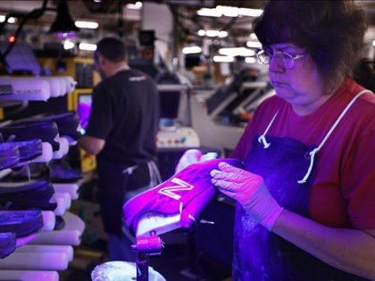 FILE- In this Dec. 17, 2018 photo, Laurie French applies adhesive under an ultraviolet light to a pair of athletic shoes designed for the military at a New Balance factory in Norridgewock, Maine. On Friday, Feb. 15, 2019, the Federal Reserve reports on U.S. industrial production for January. (AP Photo/Robert …