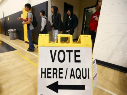 In this March 5, 2020, photo students line up to participate in budget participation election at Maryvale High School on in Phoenix. At the school hundreds of students who will turn 18 before Election Day were registered to vote. (AP Photo/Ross D. Franklin)