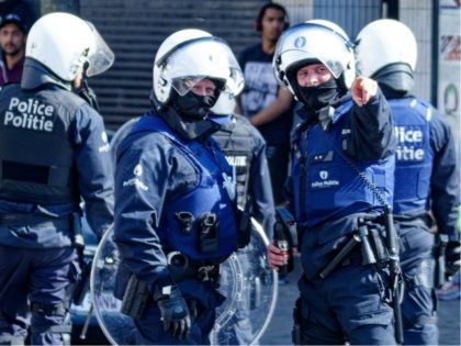 Belgian police officers wearing protective gears stand at the site of unrests in Anderlecht, Brussels, on April 11, 2020. - People gather in a reaction to the death of a 19-year-old young man, who died after his scooter collided with a police car during a chase the night before. (Photo …