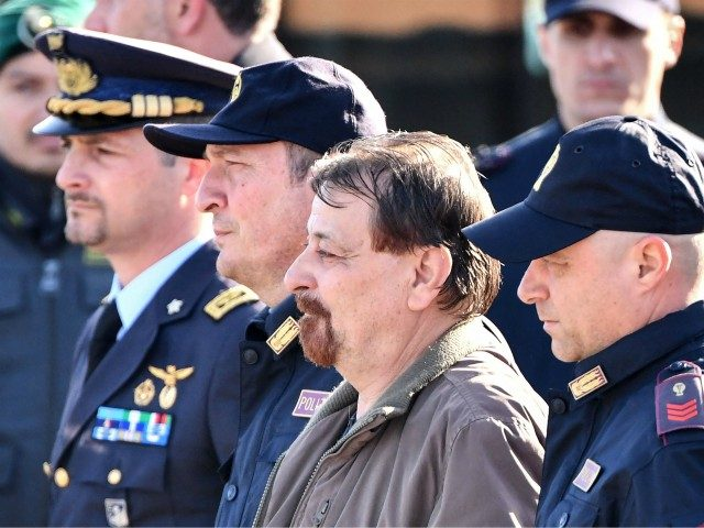 Italian former communist militant Cesare Battisti (C), wanted in Rome for four murders attributed to a far-left group in the 1970s, is escorted by Italian Police officers from an airport facility into a Police car bound for Rome's Rebbibia prison, after landing in a plane coming from Bolivia and chartered …