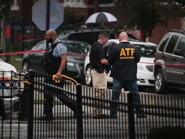 CHICAGO, ILLINOIS - JULY 21: An ATF agent and Police investigate the scene of a shooting in the Auburn Gresham neighborhood on July 21, 2020 in Chicago, Illinois. At least 14 people were transported to area hospitals after several gunmen opened fire on mourners standing outside of a funeral home. …