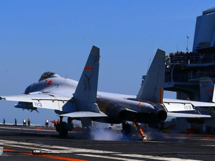 "This photo taken on April 24, 2018 shows a J15 fighter jet landing on China's sole operational aircraft carrier, the Liaoning, during a drill at sea. - A flotilla of Chinese naval vessels held a ""live combat drill"" in the East China Sea, state media reported early April 23, 2018, …"