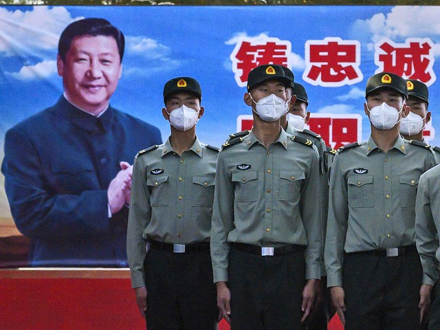 BEIJING, CHINA - MAY 20: Soldiers of the People's Liberation Army's Honour Guard Battalion wear protective masks as they stand at attention in front of photo of China's president Xi Jinping at their barracks outside the Forbidden City, near Tiananmen Square, on May 20, 2020 in Beijing, China. China's government …