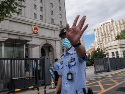 A police officer gestures before an escorted police van carrying Chinese property tycoon Ren Zhiqiang arrives at the Beijing No. 2 Intermediate People's Court on September 11, 2020, ahead of Ren's case hearing. - Ren was detained after penning an essay fiercely critical of President Xi Jinping's response to the …