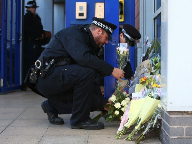 LONDON, ENGLAND - SEPTEMBER 25: Metropolitan Police collect floral tributes at Croydon Custody Centre on September 25, 2020 in the Croydon area of London, England. A murder investigation has been launched following the death of a police officer at the Croydon Custody Centre in south London. He was shot by …