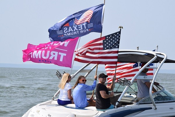 Jason and Sherry Pierce fly the Texas for Trump and Women for Trump flags during the Trump Boat Parade on Lake Livingston. (Photo: Lana Shadwick/Breitbart Texas)