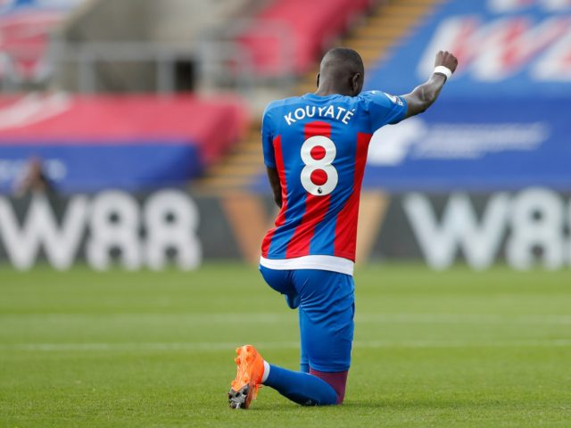 Crystal Palace's Cheikhou Kouyate takes a knee prior to the English Premier League soccer match between Crystal Palace and Southampton, at Selhurst Park, London, Saturday, Sept. 12, 2020. (AP Photo/Alastair Grant)