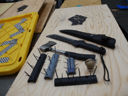 Officers recover weapons, shields, and spike strips during park cleanup.