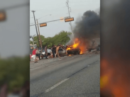 Dallas, Texas, police worked with a group of citizens to pull a man from a burning car after a six-vehicle crash, according to a video of the incident.