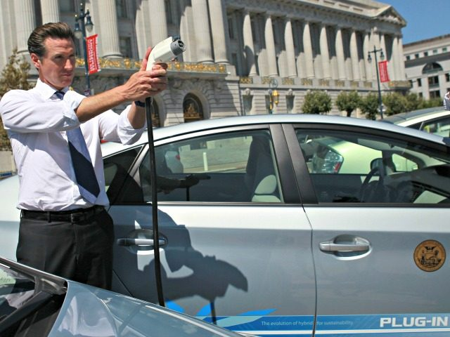 SAN FRANCISCO - AUGUST 25: San Francisco mayor Gavin Newsom holds a power cable before test driving a plug-in version of the popular Toyota Prius that is one of four on loan to the city for evaluation August 25, 2010 in San Francisco, California. With sales of electric and plug-in …
