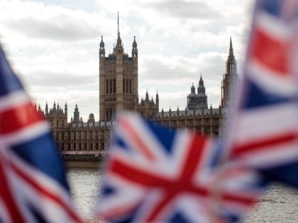LONDON, ENGLAND - MARCH 26: Union Jack flags flutter in the wind in front of the Houses of Parliament in Westminster on March 26, 2019 in London, England. British Prime Minister Theresa May is facing increased pressure to resign as she continues her attempts to pass a Brexit deal through …
