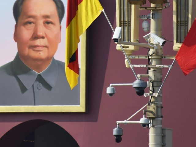 The German flag hangs next to surveillance cameras and the portrait of late communist leader Mao Zedong in Tiananmen Square in Beijing on September 6, 2019. German Chancellor Angela Merkel is currently visiting Beijing. - Some Beijing karaoke bars are closing, toy bombs are banned and every delivery package is …