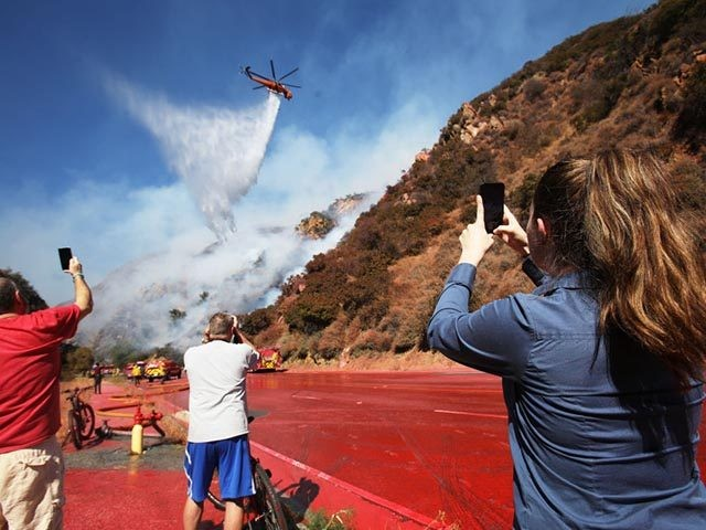 LOS ANGELES, CALIFORNIA - OCTOBER 21: Onlookers take photos as a firefighting helicopter makes a water drop over a wildfire threatening a nearby hillside home in the Pacific Palisades neighborhood on October 21, 2019 in Los Angeles, California. The roadway is covered with the fire retardant Phos-Chek which was dropped …