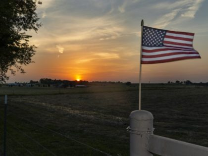 An American flag on the fence of a farm near the city of Commerce in the State of Oklahoma, at sunset, USA.